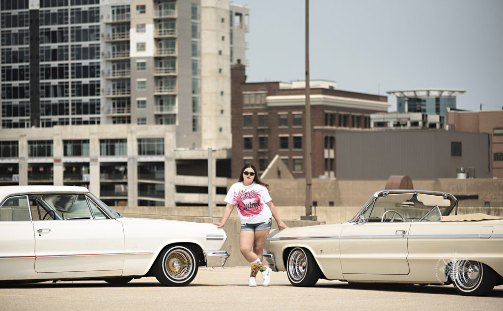 West Michigan teenage girl poses leaning against a vintage car on top of a parking garage in Kalamazoo. She is going to celebrate her quinceañera.
