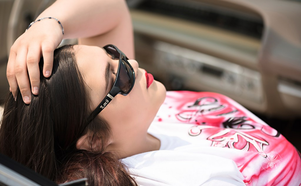 West Michigan teenage girl poses leaning against a vintage car on top of a parking garage in Kalamazoo. She wears sunglasses and red lipstick.