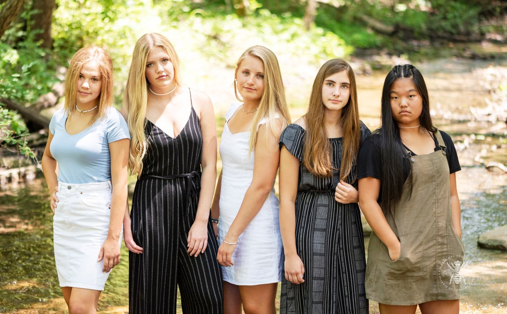 Kalamazoo Christian friend session. Senior girls wear black, white, blue, and brown colors. They pose together in a forest in West Michigan.