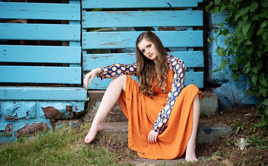 Model poses crouching in front of a blue wall. She wears an orange dress layered over a retro blue and orange patterned top.
