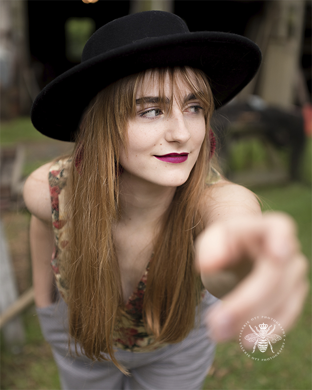 Mattawan senior girl poses with her arm reaching towards the camera. She wears a black hat and red lipstick. She poses in an abandoned location in West Michigan.