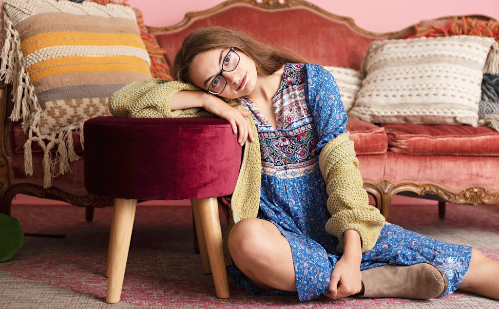 Model poses in front of a vintage couch at Therapy Boutique in Portage, Michigan. She wears a boho, blue patterned dress and a yellow cardigan.