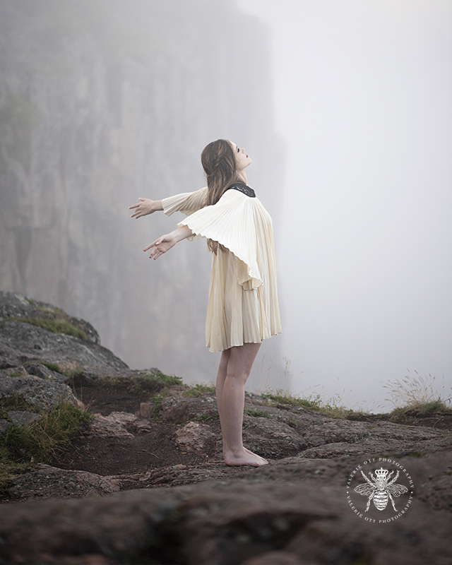 Senior girl poses standing on a foggy cliff with her arms flying behind her. She wears a cream colored flowing dress.