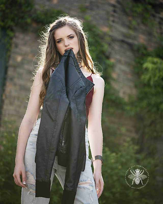 Model wears a red top and denim jeans. She stands in front of a vine covered building. She poses holding a leather jacket in her mouth.