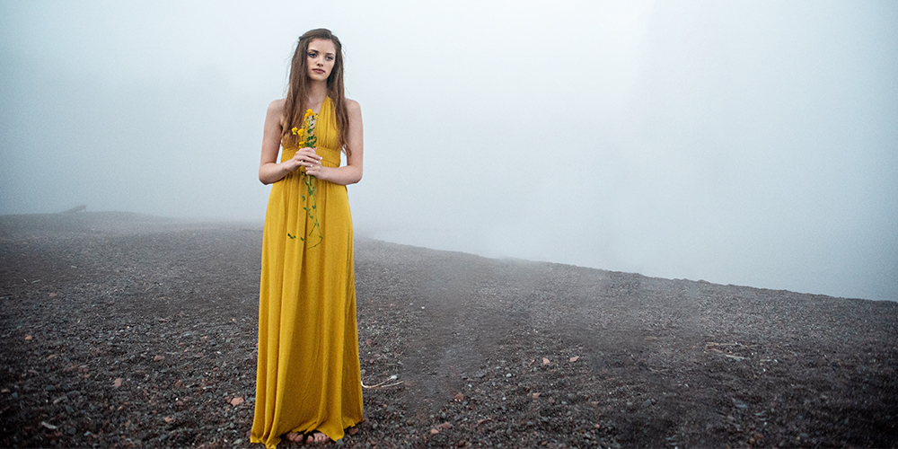 Senior girl poses on a foggy beach. She wears a yellow dress and holds a small bouquet of yellow flowers.