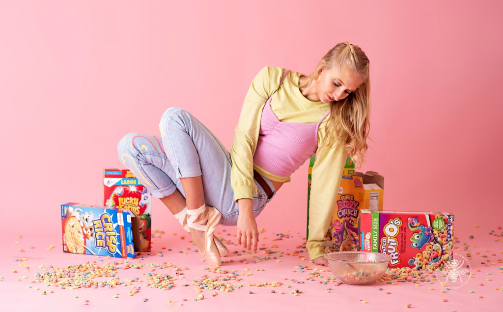 Western Michigan University dancer poses in painted jeans and ballet slippers. She poses in front of a pink background.