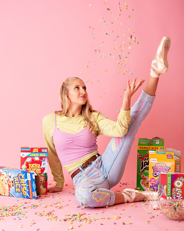 Western Michigan University dancer poses with her ballet pointe shoes and throws cereal in her mouth in front of a pink background.