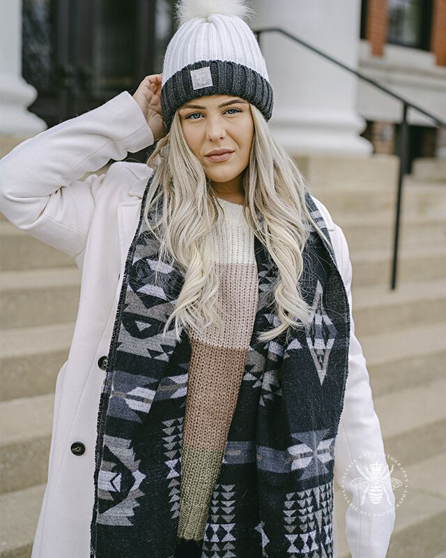 Western Michigan University winter senior session. Senior wears a hat, patterned scarf, and a coat. She poses by the steps on campus.