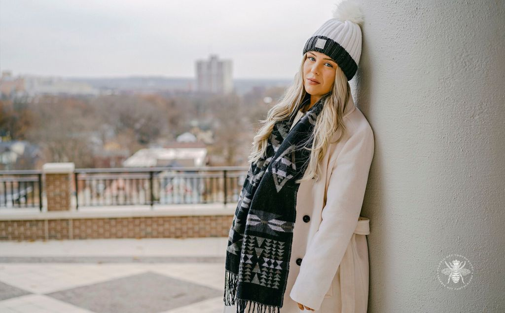Western Michigan University winter senior session. Senior wears a hat, patterned scarf, and a coat. She poses on campus.
