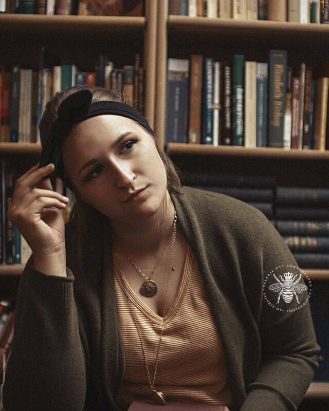 Mattawan senior girl poses in front of a bookshelf in a cozy bookstore. She wears layered necklaces, a cardigan, and a headband.