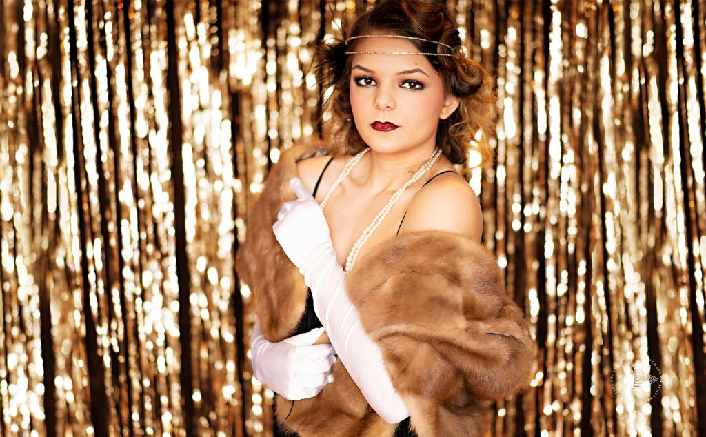 Mattawan senior poses for styled session in West Michigan. She wears her hair in pin curls, red lipstick, white gloves, pearl necklaces, a feather boa, and a flapper dress. She stands wrapped in a shawl in front of a shimmering gold backdrop.