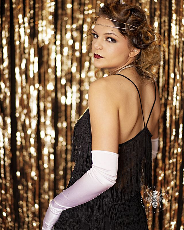 Mattawan senior poses in West Michigan. She wears her hair in pin curls, red lipstick, white gloves, pearl necklaces, a feather boa, and a flapper dress. She stands in front of a shimmering gold backdrop.