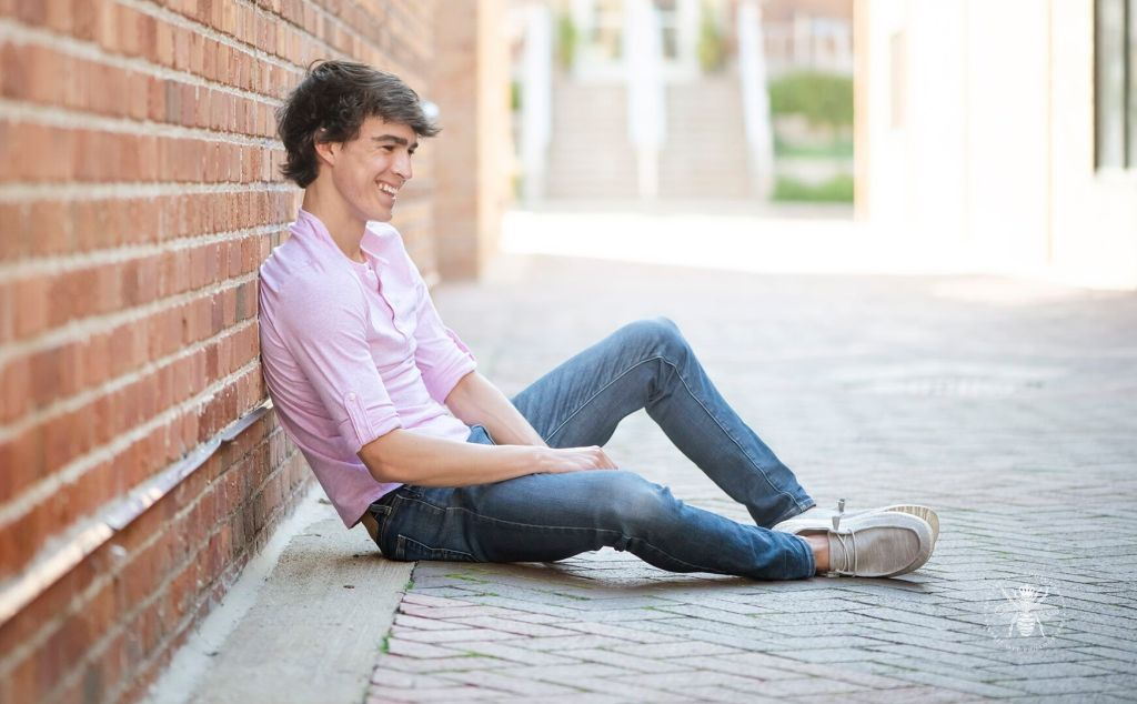 Portage Northern senior guy poses sitting against a brick wall in Downtown Kalamazoo. He wears jeans and a pink shirt.