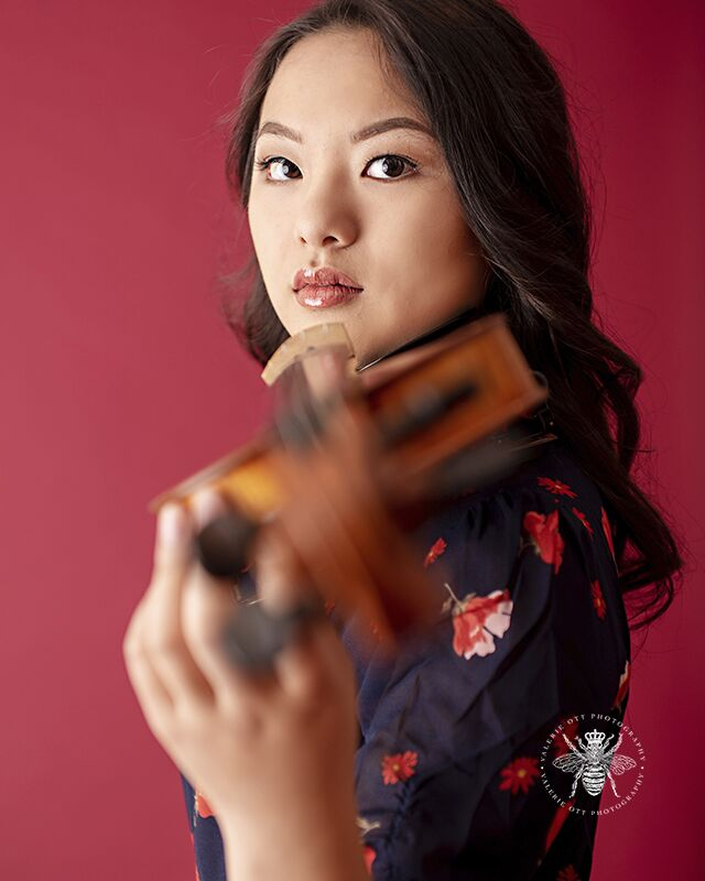 Portage Central high school girl poses playing the violin in front of a red background in a studio. She wears a black dress with a red floral print.