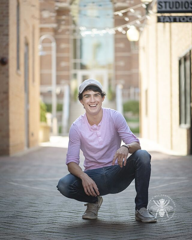 Portage Northern senior guy poses smiling and kneeling. He wears jeans and a pink t shirt.