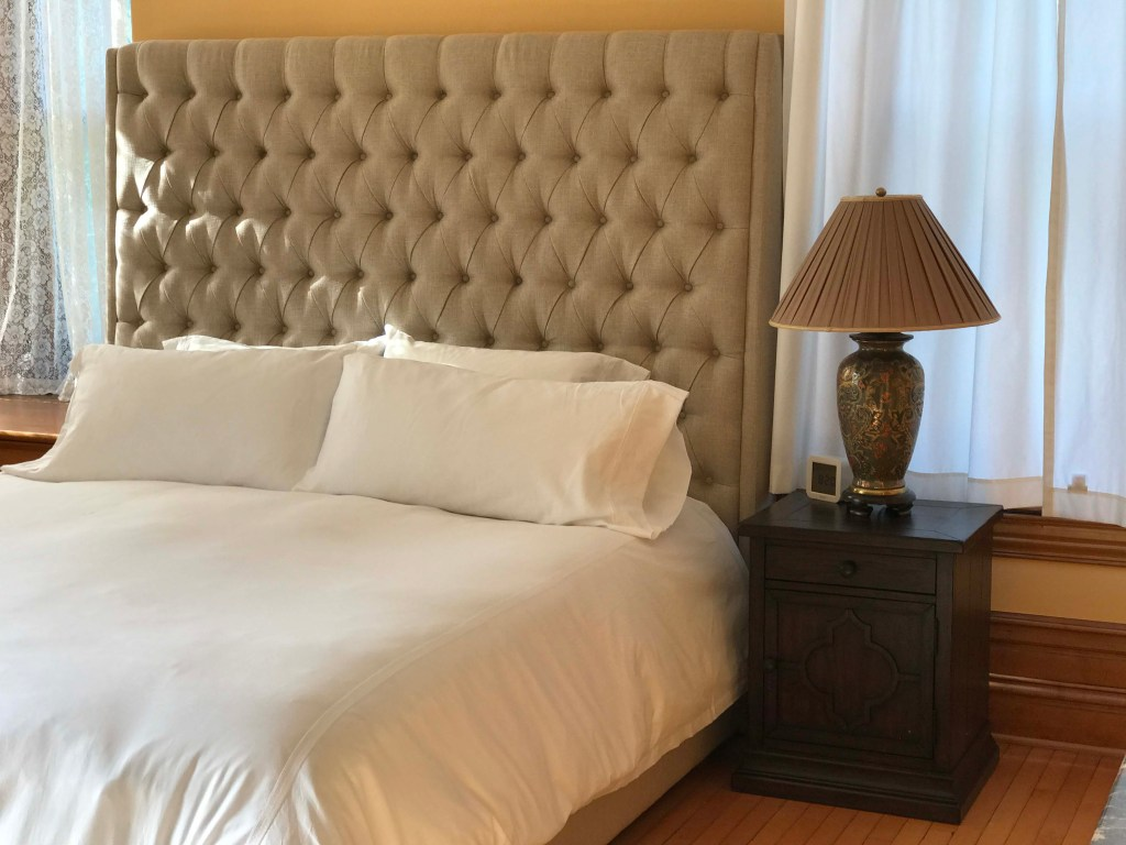 Upholstered headboard and comfy bedding await your stay in the Maple Suite of Castle La Crosse.