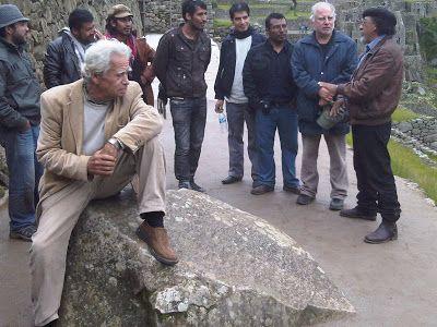 El poeta Rodolfo Hinostroza sentado sobre una piedra milenaria en Cusco, mientras Vladimir Herrera (casaca de cuero marrón) comenta.