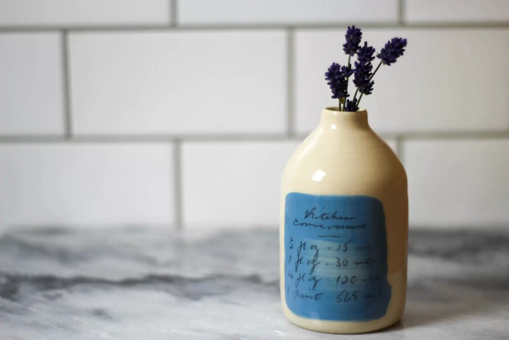 Ceramic milk bottle with kitchen conversions. Display on it's own or with a decorative flower.