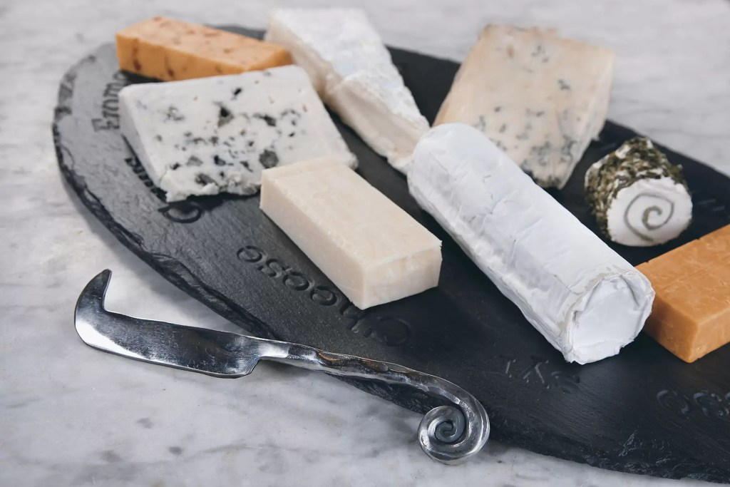A selection of cheeses served on a Welsh slate cheeseboard. A thoughtful personalised wedding gift.