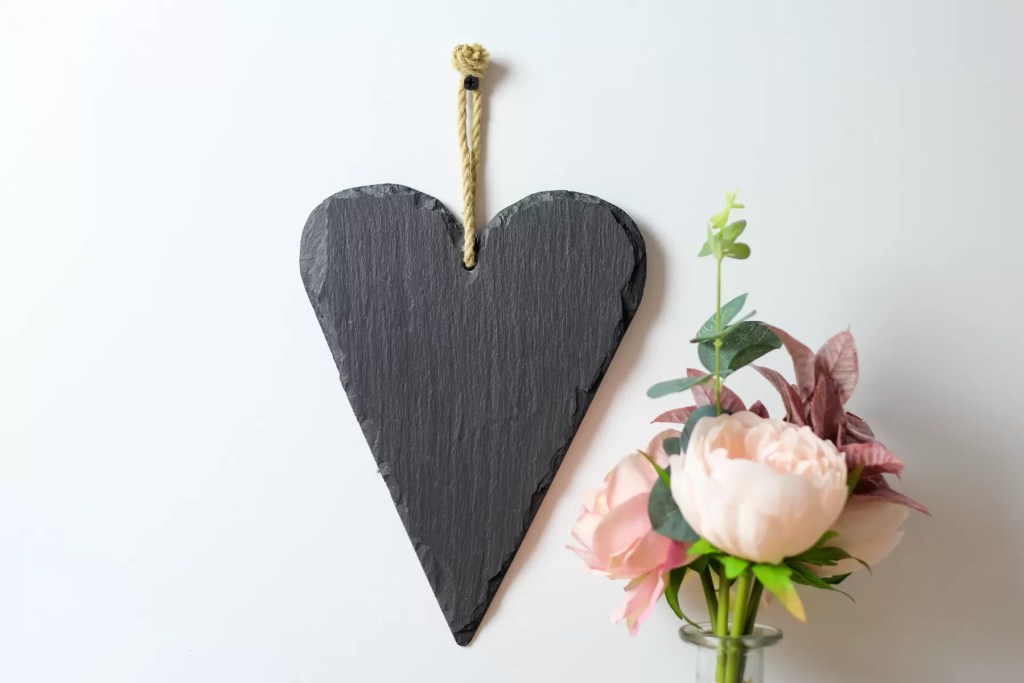 Welsh slate heart hanging on a wall with hemp rope.