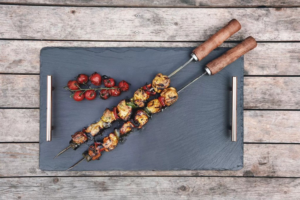 Welsh slate serving tray with chicken and pepper kebabs placed on top