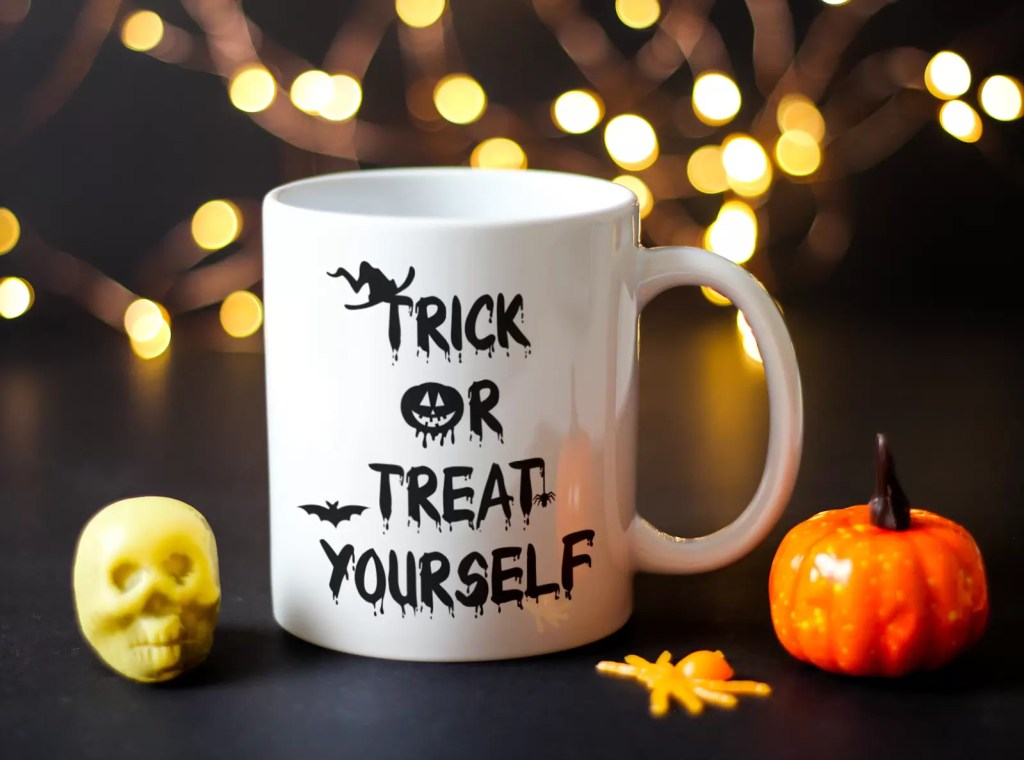 White ceramic Halloween mug which says trick or treat yourself