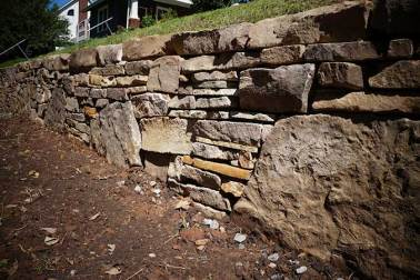 Boulders placed in a dry-stacked stone wall