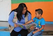 mujer enseñando un libro a un niño