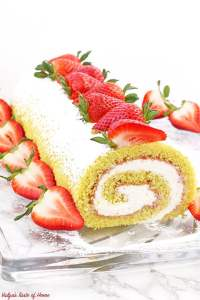This Strawberry Vanilla Swiss Roll Recipe is the easiest and the quickest dessert you can ever make! Supper soft sponge cake topped with amazingly tasty (no cook) strawberry sauce, filled with super soft and fluffy cream, dusted with confectioners' sugar and topped with loads of fresh strawberries.