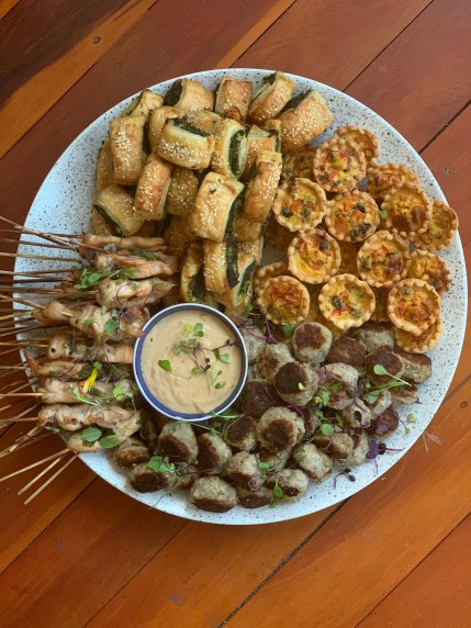 Spinach puffs, mini quiche, meatballs and satay chicken on a large mixed platter