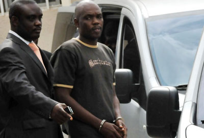 One  of  the  four  Abuja  blasts  suspects, Mr  Charles  Tombrah  Okah, in  handcuffs,  being  led  out  of  the  Federal Capital Territory Chief Magistrates Court, Wuse Zone 6, yesterday in Abuja