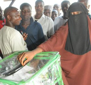 A woman in Purdah casting her votes during the Gubernatorial and State Assembly Elections in Minna, Niger State. Photo by Abayomi Adeshida