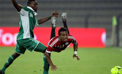 Egypt's Mohammed Abdel Shafi (R) is fouled by Nigeria's Daniel Akpeyi during their friendly football match in the Gulf emirate of Dubai on April 12, 2012. Egypt 3  Nigeria 2. AFP PHOTO