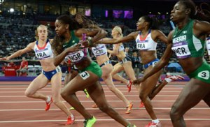 File Photo: Nigeria's Ajoke Odumosu (R) hands the baton to Regina George as they compete in the women's 4X400 relay final of the London 2012 Olympic Games in London. PHOTO - AFP.