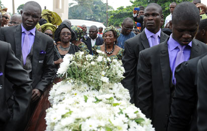 The widow Professor Christie Achebe walks behind the coffin of late literary icon Professor Chinua Achebe during the funeral at Ogidi, Anambra State. AFP PHOTO.