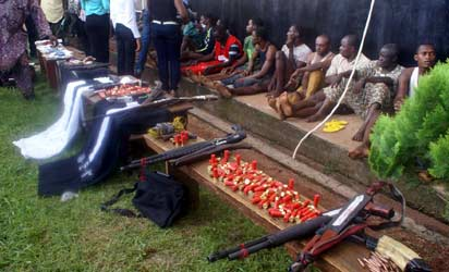 Some of the suspects and weapons recovered by the Edo State Police Command during the parade of 32 suspected robbers and kidnappers in Benin City, yesterday. Photo: Barnabas Uzosike.