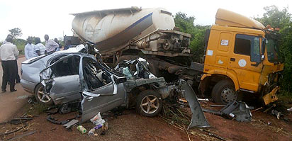 *The mangled remains of the car after it collided with the trailer leaving its occupants dead. INSET: The late Victor Idam