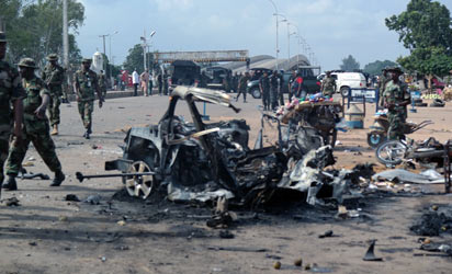 Military officers walk past the remains of a car after an explosion on July 23, 2014 in Kaduna, north of Nigeria. A second blast  in the city has killed at least 17 people, the national rescue agency said, after an earlier suicide attack in the city killed at least 25. An around-the-clock curfew was announced for the city after the bombings