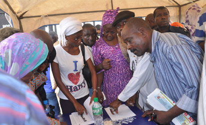 Lagosians checking their names on the INEC list of permanent voters cards (PVC) around 3 pm. at Sunday Adigun  polling Unit, Alausa, Ikeja yesterday.