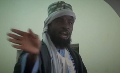 A screengrab taken on November 9, 2014 from a new Boko Haram video released by the Nigerian Islamist extremist group Boko Haram and obtained by AFP shows the leader of the Nigerian Islamist extremist group Boko Haram, Abubakar Shekau preaching to locals in an unidentified town. Shekau again dismisses government claims about ceasefire talks and threatens to kill the man who has presented himself as Boko Haram's negotiator.  AFP PHOTO