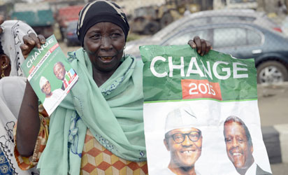 "A mother carries banner to drum support for the leading opposition All Progressives Congress presidential candidate Mohammadu Buhari and running mate Yemi Osinbajo during a rally christened 'Walk for Change"" in Lagos, on March 7, 2015 in Lagos, Nigeria's commercial capital.   Presidential elections scheduled for February 14 were delayed for six weeks as the military said the ongoing counter-offensive against Islamists Boko Haram meant that troops could not provide security on polling day. AFP PHOTO"