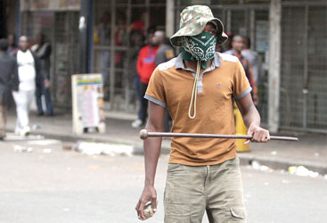 """A local resident holds a stone and a traditonal Zulu weapon after a skirmish with foreigners as thousands of people take part in the """"peace march"""" against xenophobia in Durban, South Africa, on April 16, 2015. South African President Jacob Zuma on April 16 appealed for the end of attacks on immigrants as a wave of violence that has left at least six people dead threatened to spread across the country. In the past two weeks, shops and homes owned by Somalis, Ethiopians, Malawians and other immigrants in Durban and surrounding townships have been targeted, forcing families to flee to camps protected by armed guards. AFP PHOTO"""