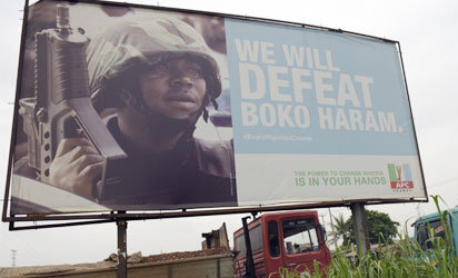 "A photo shows a campaign signboad displayed by the ruling All Progressives Congress (APC) to show its readiness to defeat Boko Haram Islamists on assumption office at Ogijo, Ogun State in southwest Nigeria, on July 3, 2015. Boko Haram carried out a fresh wave of massacres in northeastern Nigeria on July 3, locals said, killing nearly 200 people in 48 hours of violence President Muhammadu Buhari blasted as ""inhuman and barbaric"". AFP PHOTO"