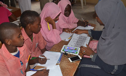 AUN student teaching pupils in Wuro Hausa Primary School in Yola, Adamawa State with tablets in local languages