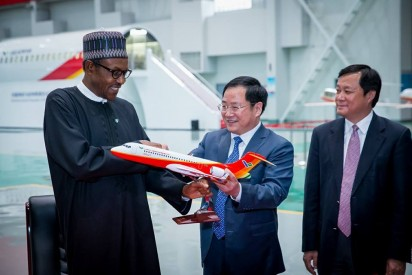 President Buhari receiving a presentation from Mr Jin Zhuanglong Board Chairman, Commercial Aircraft Corporation of China shortly after his visit to Commercial Aircraft Cooperation of China Ltd in Shanghai China.