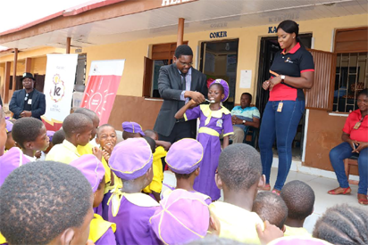 L-R Dr. Abolade Majekodunmi of Hygeia HMO demonstrating with a pupil on how to wash teeth during PCSR activities at Coker Primary School Ifako Ijaye and Kenchukwu Okafor of Corporate Communications Ikeja Electric watching the exercise.