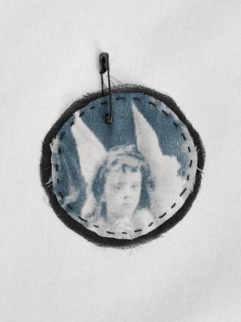 Ann Demeulemeester circle brooch with cherub print stitched onto black silk — fall 2005