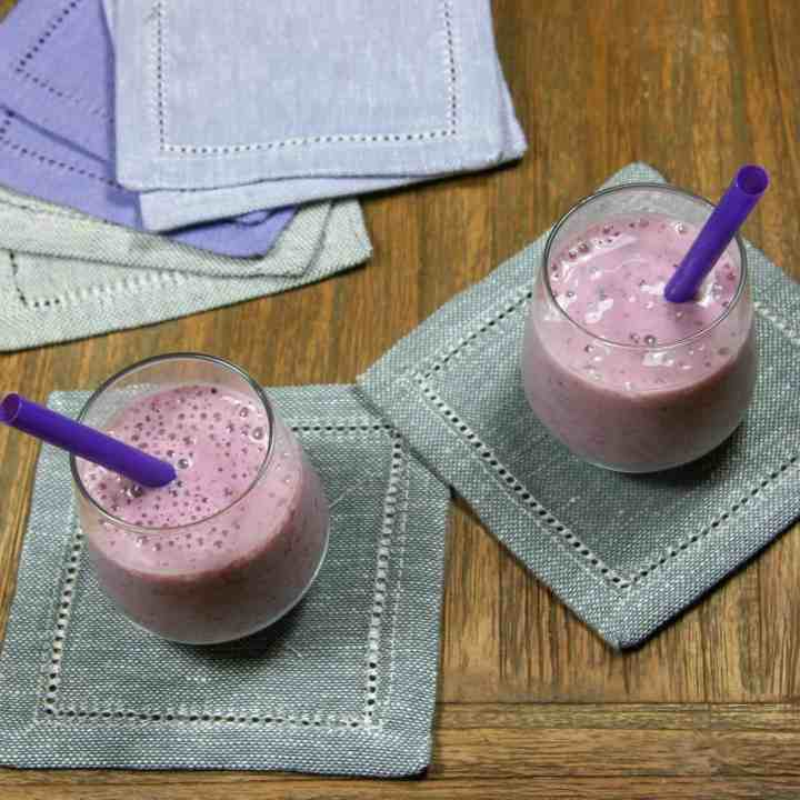 two small strawberry blueberry banana smoothies on napkins with straws