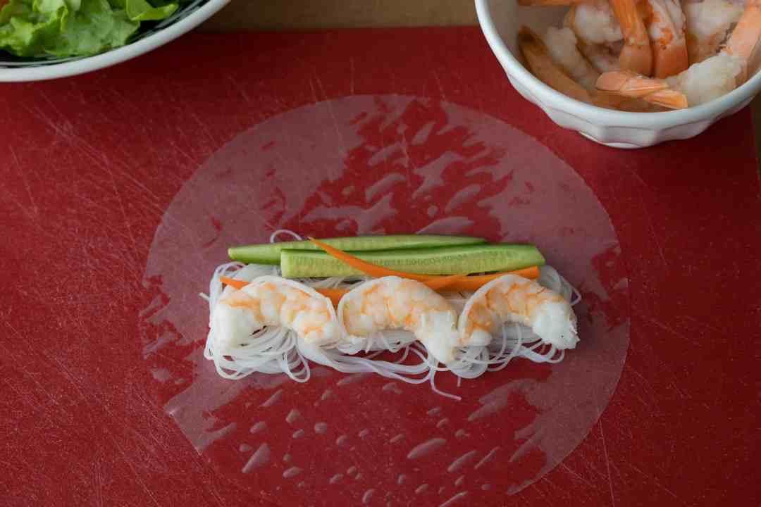 first step of spring roll filling process: add noodles, shrimp, veggies