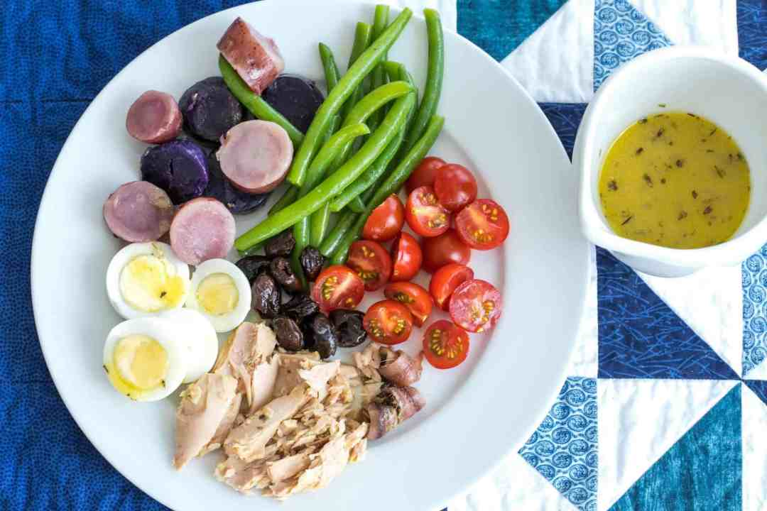 nicoise salad with tuna, eggs, green beans, potatoes, olives, and cherry tomatoes